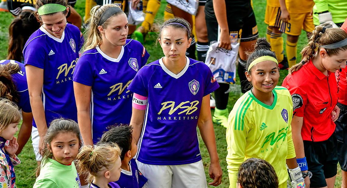Maggie Miller (second from left) and Gabriela Lopez (in yellow) enter Saturday's game.