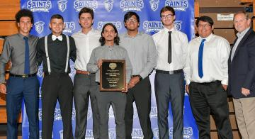 The tennis team is pictured with Athletic Director Jack Hank. Pegas is shown holding the 2016 conference plaque.