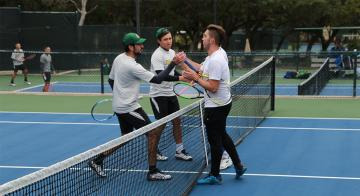 The Saints players shake hands after a doubles match.